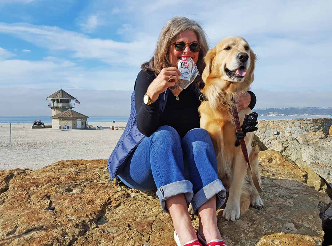 Sarah Richie-Holder, a longtime Coronado resident, is seen here with her dog Macky, at Coronado's Central Beach, showing off their Bluewater Boathouse doggie bag.