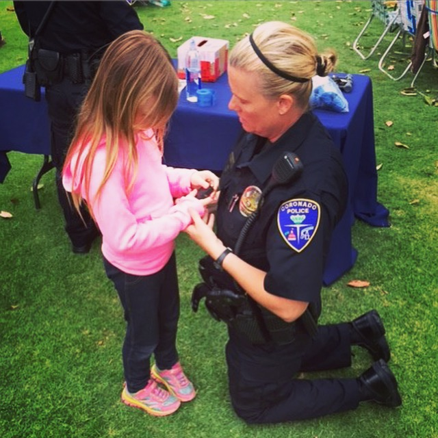 "(Photo courtesy of Julie Dabbieri) Grace with Coronado Police Officer Sheri at a concert in the park. Grace's mom Julie said, ""Officer Sheri took the time to show Grace her badge, gun, and even bullets, letting her feel everything. I really want to give the city a lot of praise for being not only supportive, but also accommodating in a very 'hands on' way."""