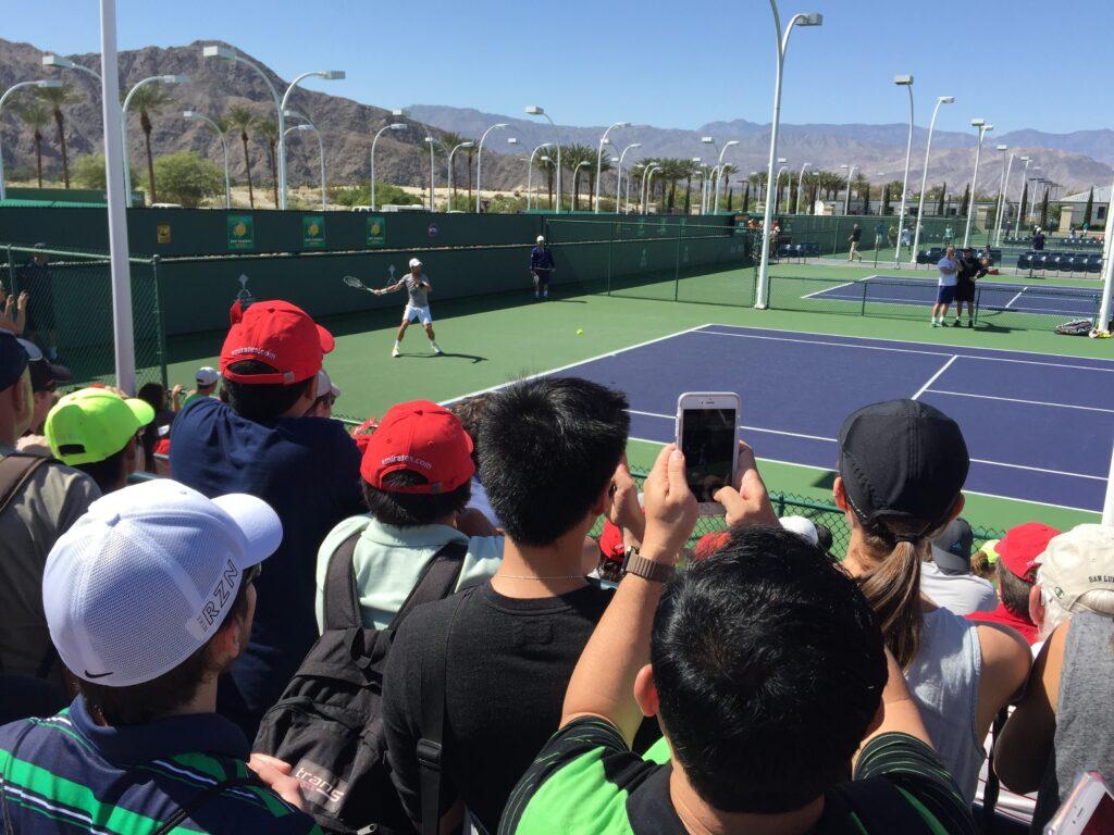 Spectators crowd around the practice court to watch #1 player in the word, Novak Djokovic, warm up.