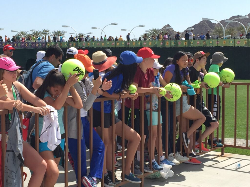 """Kids waiting """"patiently"""" to get autographs from their favorite players. Note, big tennis ball is going to cost $35 plus $1 for a Sharpie."""