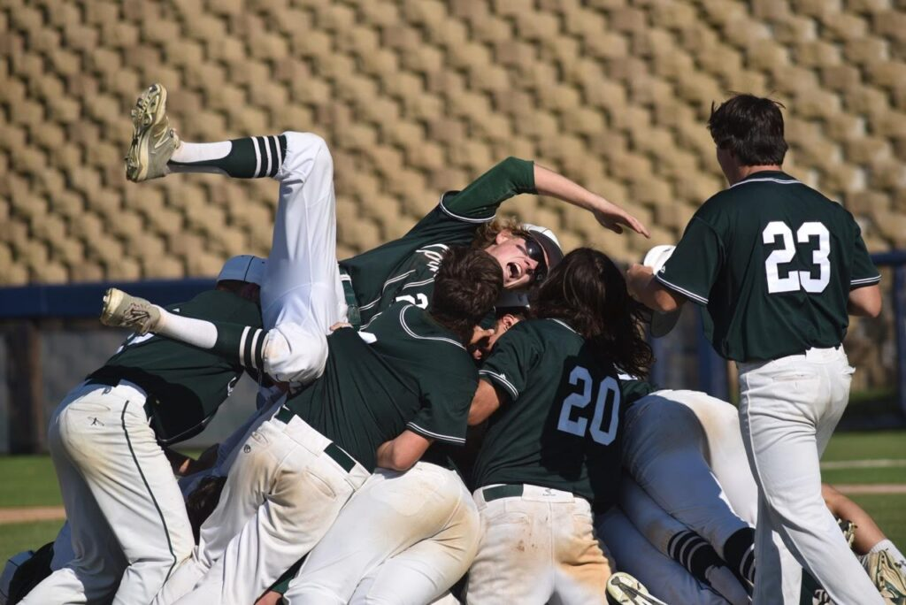 Outfielder Chris Cummins joins the Islanders players as they celebrate their victory in the CIF Division III championship game Friday June 3rd at USD's Fowler Park.  (Photo:  Joan Fahrenthold)