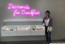 "Lucia Mouet Stands Inside Coronado Store by display case and sign ""Diamonds For Breakfast"""