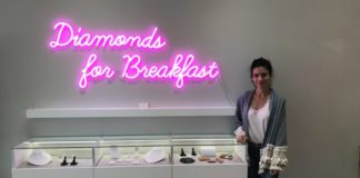 """Lucia Mouet Stands Inside Coronado Store by display case and sign """"Diamonds For Breakfast"""""""