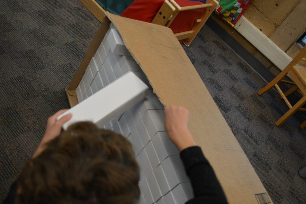 Volunteers put small white boxes into larder cardboard box