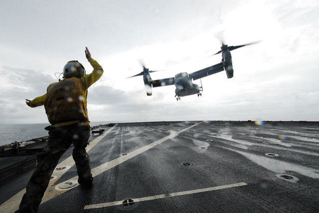 LEYTE GULF (Nov. 22 2013) Aviation Boatswain's Mate (Handling) Airman Jennifer L. Confer, from Buffalo, N.Y., directs a V-22 Osprey as it lifts off from the amphibious dock landing ship USS Ashland (LSD 48). This is the first-ever launch of an Osprey from the ship. Ashland is off the coast of the Philippines assisting in Typhoon Haiyan recovery efforts. (U.S. Navy photo by Chief Mass Communication Specialist Allen Onstott/Released)
