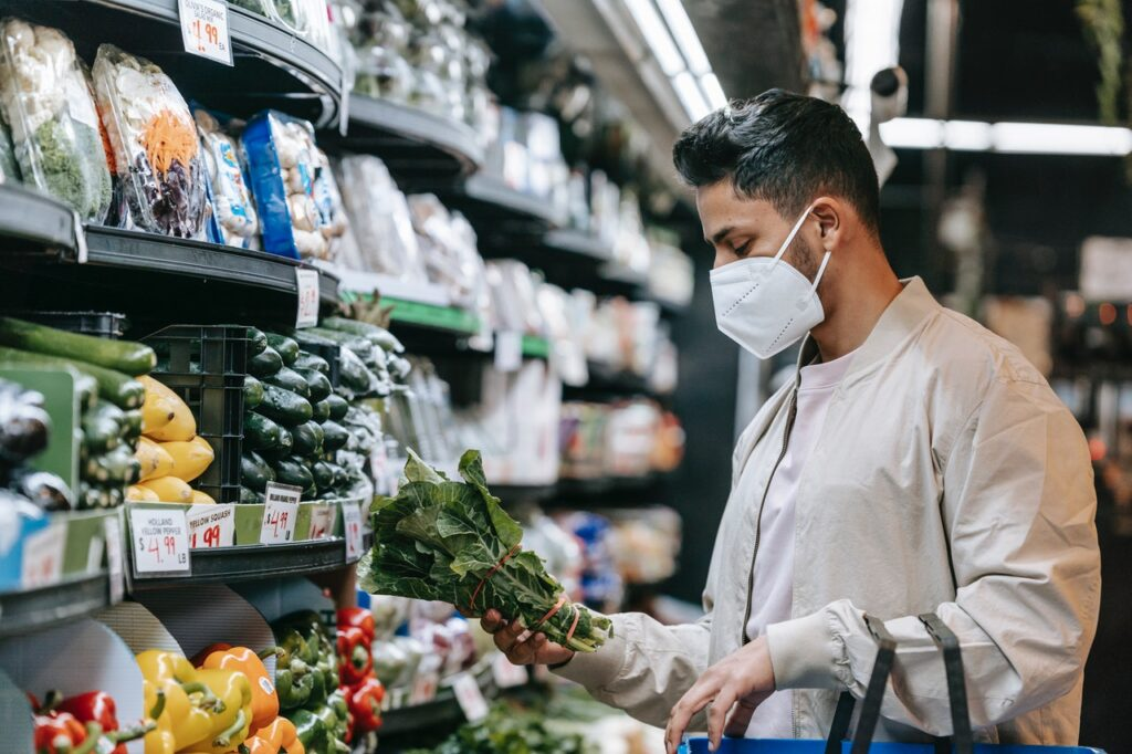 man grocery shopping in mask